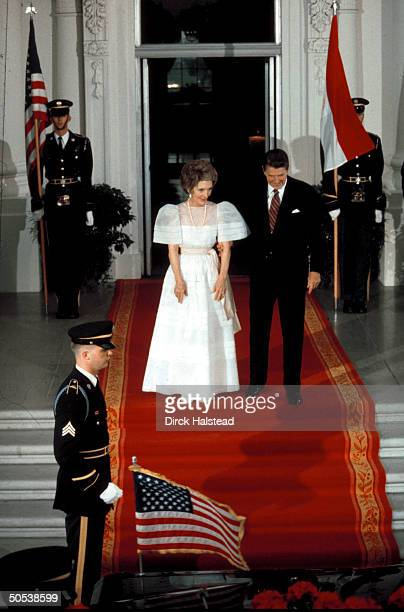 President Ronald Reagan and wife Nancy standing on red carpet as they await the arrival of Egyptian president Anwar Sadat to the White House for a...