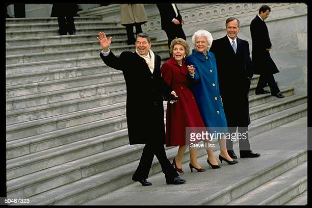 President Ronald Reagan and wife Nancy walking down steps, hand-in-hand, accompanied by President George H. W. Bush and his wife Barbara, leaving the...