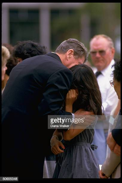 President Ronald Reagan embracing daughter of one of the crew members who died in the space shuttle Challenger disaster during memorial service