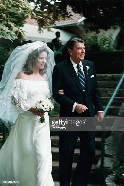 President Ronald Reagan escorts his daughter, the soon to be Patti Davis, in her wedding dress, outside.