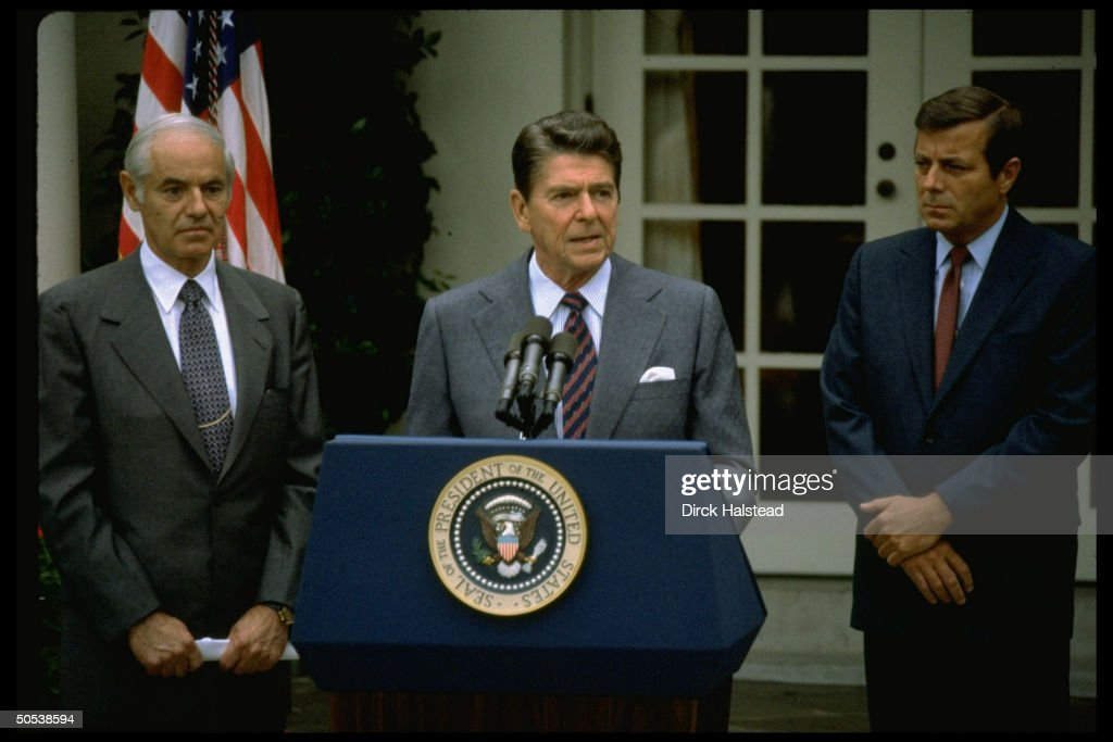 President Ronald Reagan (C), flanked by Andrew Lewis (R) and William French Smith, speaking out against the unauthorized air traffic controller strike while standing at podium in rose garden at the White House.