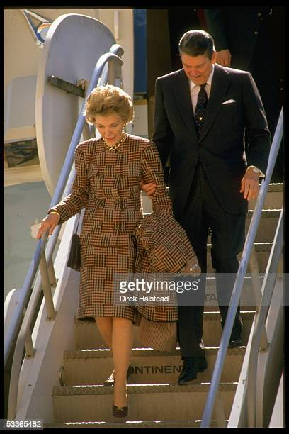 President Ronald Reagan holding arm of wife Nancy clad in a plaid Bill Blass suit estimated to cost $4000 as they carefully walk down airplane steps