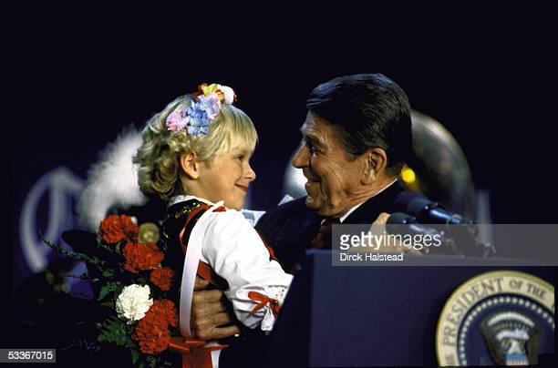 President Ronald Reagan holding child Jennifer Wjciechowski after she presented him flowers at a campaign speech