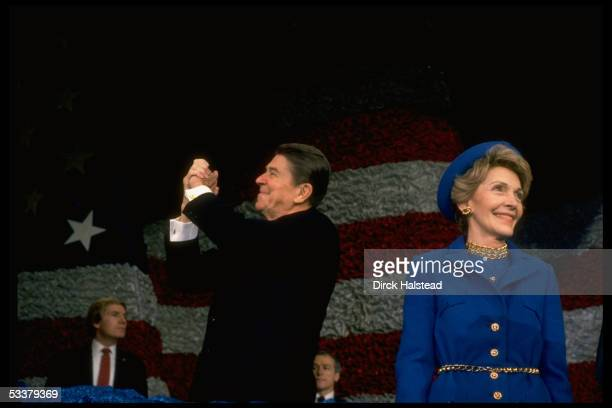 President Ronald Reagan holding up arms victoriously as wife Nancy looks on at postinaugural gathering of marching bands at the Capitol Center