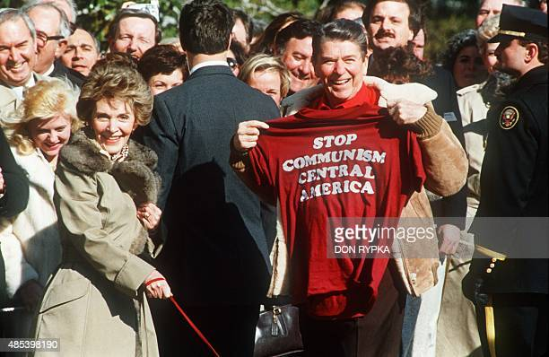 """President Ronald Reagan holds up 07 March 1986 a T-shirt with the words """"Stop Communism in Central America"""" as he and First Lady Nancy Reagan leave..."""