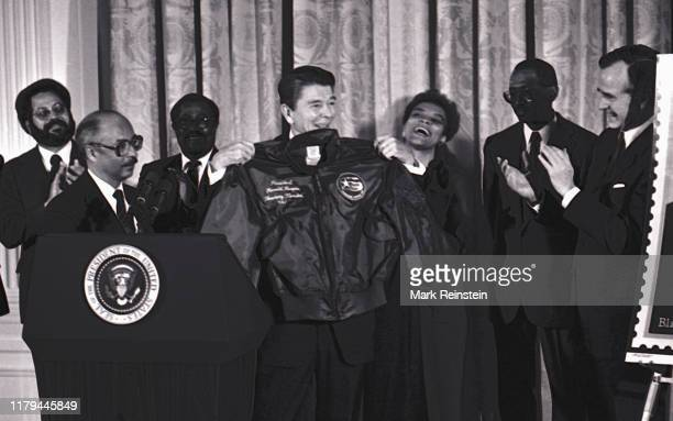 President Ronald Reagan is presented with a flight jacket by Lt Colonel Charles McGee President of the Tuskegee Airmen Association making Reagan an...