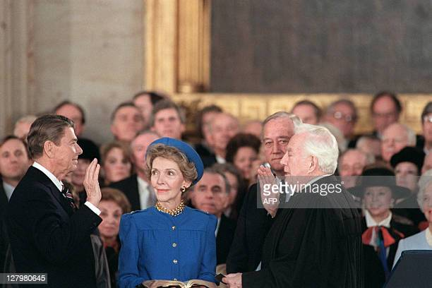 US President Ronald Reagan is sworn in as 40th President of the United States by Chief Justice Warren Burger beside his wife Nancy Reagan during...