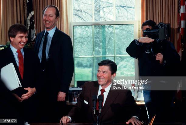 President Ronald Reagan laughs with Larry Speakes, White House Press Secretary, and Counselor David Gergen after a press conference in the Oval...
