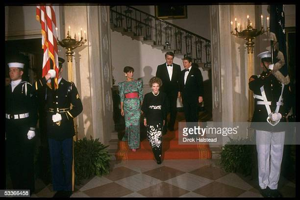 President Ronald Reagan Nancy Reagan with Canadian PM Mila Mulroney men in black tie ladies in fancy gowns descending red carpeted stairs dinner