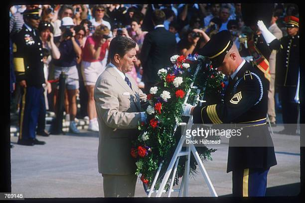 President Ronald Reagan observes Memorial Day at the National Cemetery May 27 1985 in Arlington VA Reagan's administration was marked by economic...