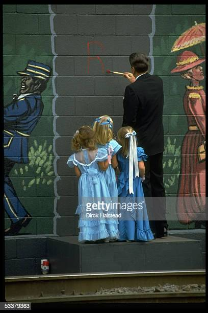 President Ronald Reagan painting his initials on a cinderblock wall as three unidentified little girls look on during his whilstlestop tour while...