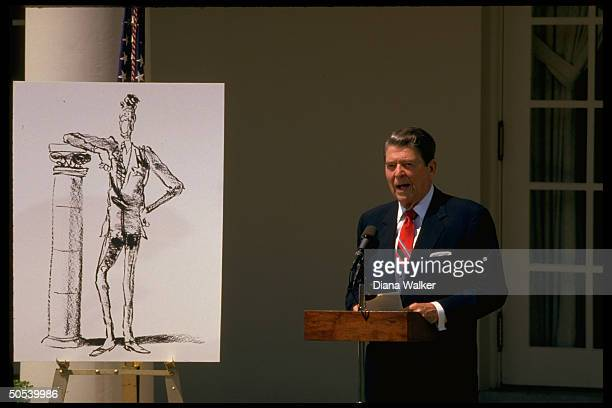 President Ronald Reagan pointing to blown up cartoon depicting himself during gettogether with cartoonists in the Rose Garden of the White House
