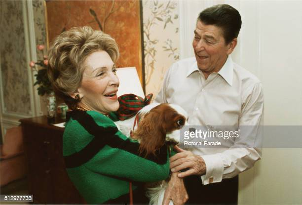 US President Ronald Reagan presents First Lady Nancy Reagan with an early Christmas present of a king charles spaniel named Rex at their suite in a...