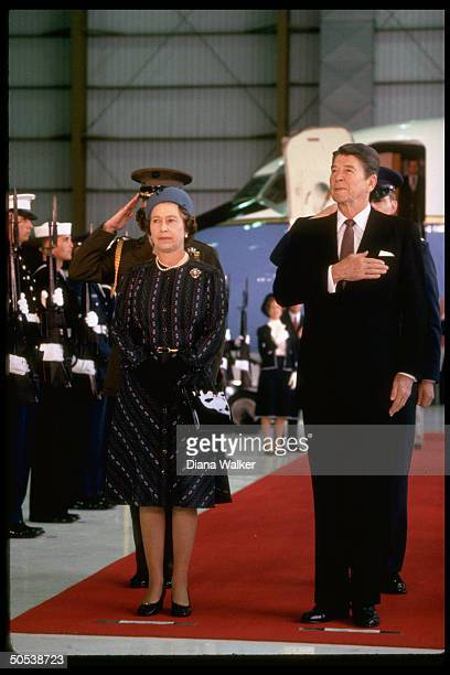 President Ronald Reagan proudly holding hand over heart during American National Anthem as he stands beside England's Queen Elizabeth II during her...