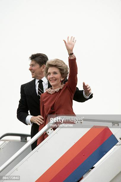 President Ronald Reagan running for reelection and First Lady Nancy Reagan wave from the top of the airplane steps as they prepare to depart for...