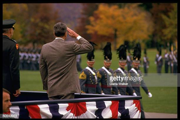 President Ronald Reagan saluting West Point cadets as they march by reviewing stand on campus