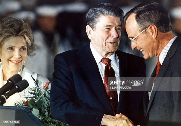 US President Ronald Reagan shakes hands with US Vice President George Bush as First Lady Nancy Reagan looks on 03 June 1988 at Andrews Air Force Base...