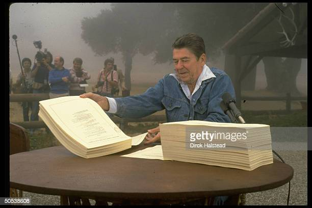 President Ronald Reagan signing tax and budget cuts while sitting outside as he vacations on his ranch