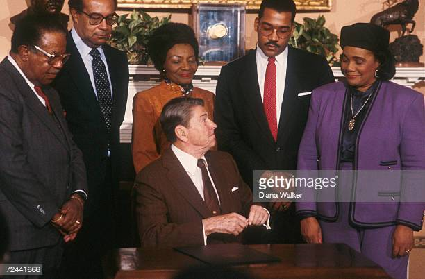 President Ronald Reagan signs the Martin Luthor King Jr Day Declaration making it a holiday as Loretta Scott King and her son Dexter King watch...