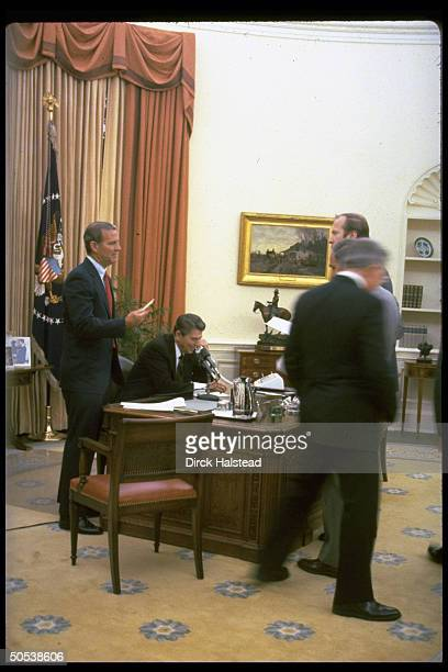 President Ronald Reagan sitting at desk surrounded by David Gergen Alexander Haig Richard Allen and James Baker at the White House after winning the...