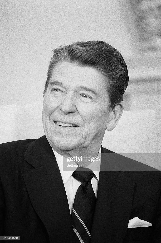President Ronald Reagan smiles and answers reporters questions regarding his post-surgery colon exam while meeting Coretta Scott King in the Oval Office.
