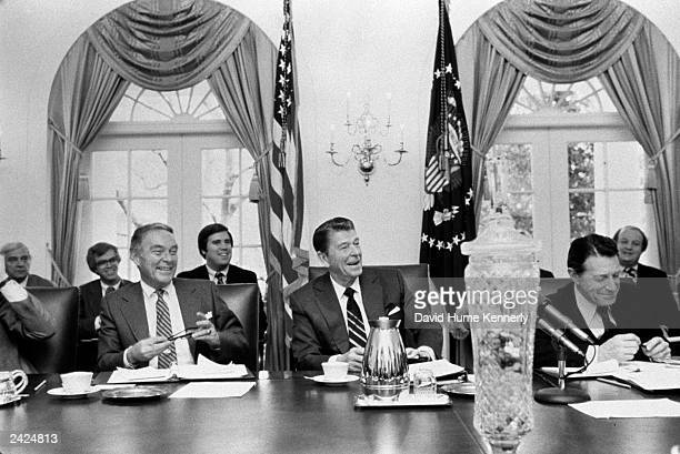 US President Ronald Reagan smiles during a cabinet meeting with Secretary of State Alexander Haig and Secretary of Defense Casper Weinberger in 1981...