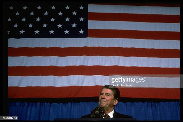 President Ronald Reagan speaking in front of large American flag at dinner to raise campaign funds for reelection of Senator Strom Thurmond