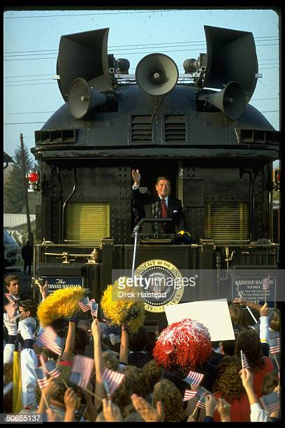 President Ronald Reagan speaking into mike while standing on former President Harry Truman's train The Ferdinand Magellan during his campaign for...