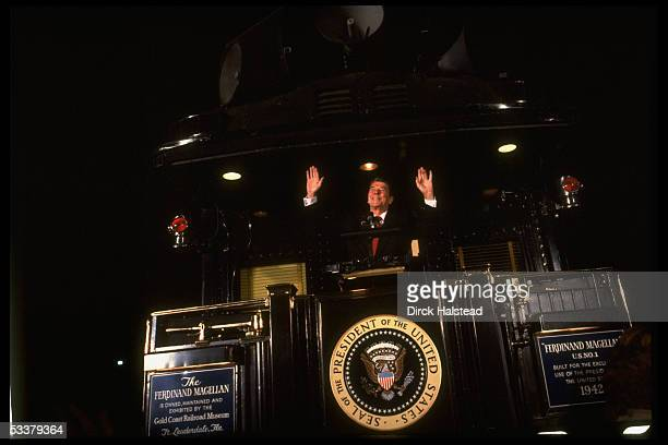 President Ronald Reagan speaking into mike while standing on former President Harry Truman's train 'The Ferdinand Magellan' during his campaign for...
