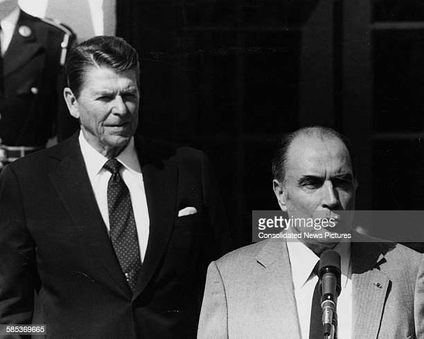 US President Ronald Reagan watching his French counterpart Francois Mitterand speaking during a press conference outside the White House Washington...