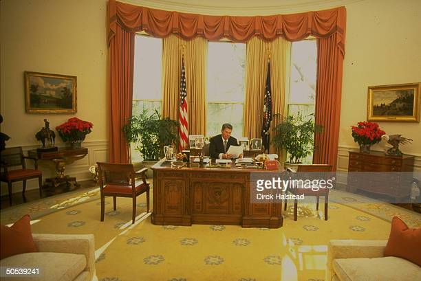 President Ronald Reagan working in the Oval Office of the White House