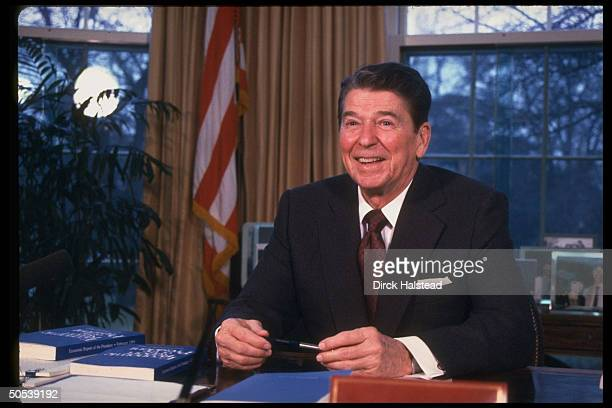 President Ronald Reagan working on economic report and legislative message at his desk in the Oval Office of the White House