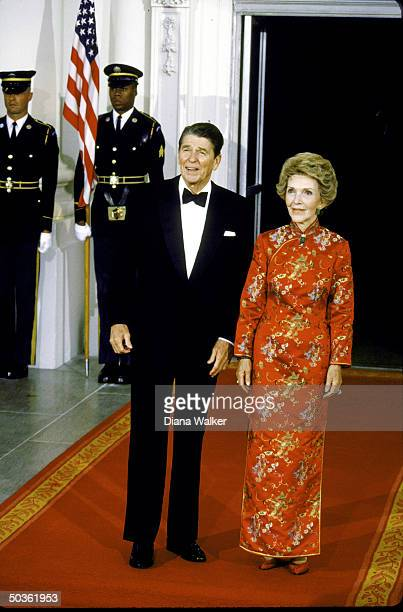 US President Ronald W Reagan in tuxedo with wife Nancy wearing red Chinesestyle gown for banquet for visiting Chinese Pres Li Xianning
