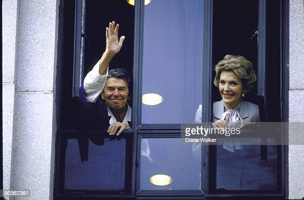 President Ronald W. Reagan waving, with wife Nancy at his side, from window at Bethesda Naval Hospital during his recovery from colon cancer surgery.