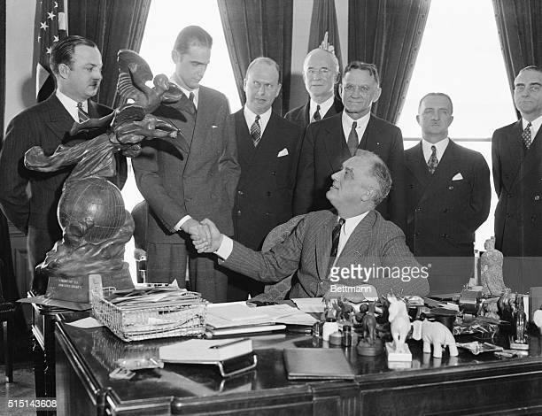 President Roosevelt presented to Howard Hughes motion picture producer and famous flyer the Harmon International Trophy in Washington DC March 2 The...