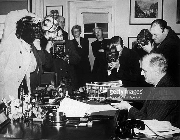 President Roosevelt signing the LeaseLend Bill at the White House Washington surrounded by photographers recording the historic event
