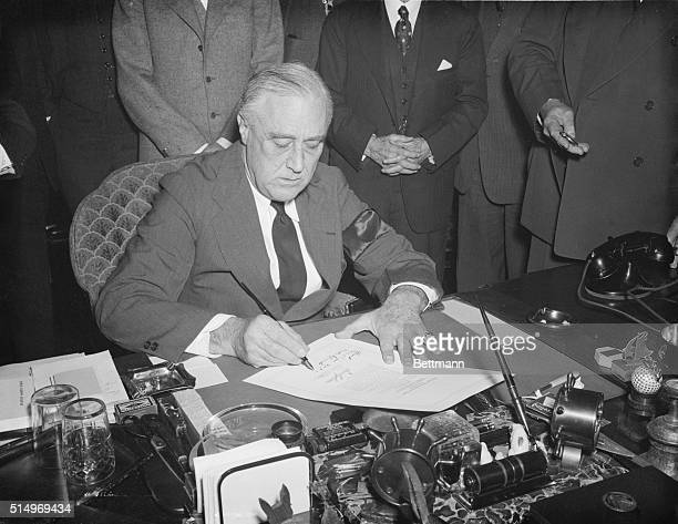 President Roosevelt signs the declaration of war against Japan after the attack on Pearl Harbor
