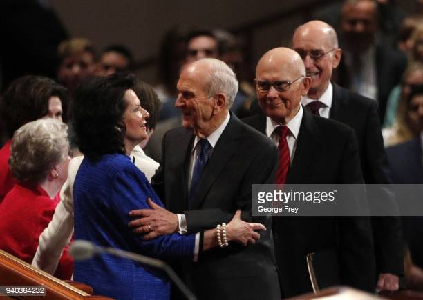 President Russell M Nelson hugs his wife Wendy as 1st Councilor Dallin H Oaks and 2nd Councilor Henry B Eyring walk into the first session of the...