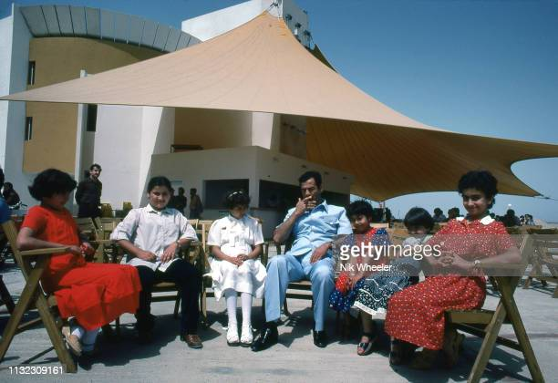 HABBANIYAH IRAQ JANUARY 1978 President Saddam Hussein of Iraq sits smoking with his children at lakeside retreat in Habbaniyah Iraq in late 1970s...