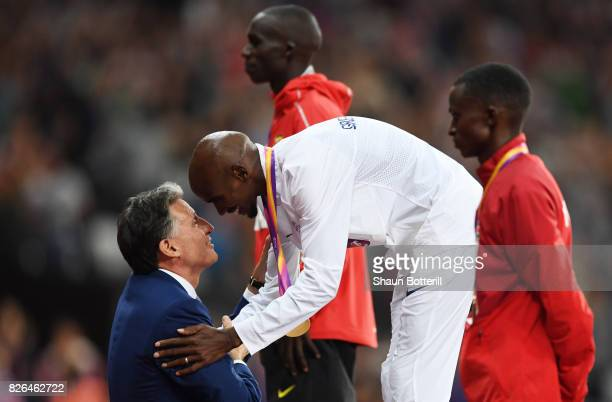 President Sebastian Coe hands Mo Farah of Great Britain his gold medal after winning the Men's 10000 metres final during day one of the 16th IAAF...