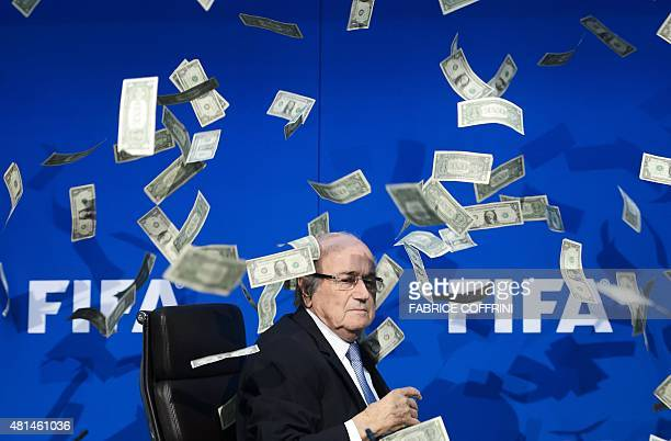 FIFA president Sepp Blatter looks on as fake dollar notes fly around him thrown by a British comedian during a press conference at the FIFA worldbody...