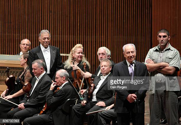 President Shimon Peres speaking to the audience with smiling conductor Zubin Mehta and musicians, members of the Israel Philharmonic Orchestra...
