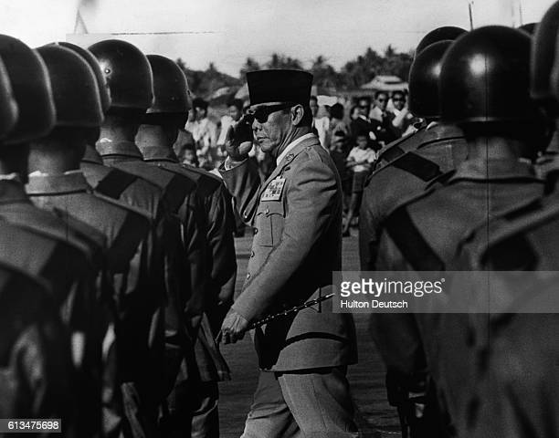 President Sukarno the first leader of Indonesia after it became a republic in 1945 inspects his troops
