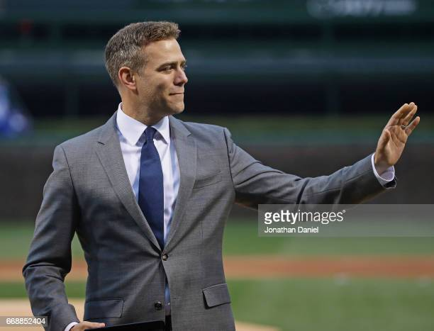 President Theo Epstein of the Chicago Cubs waves to the crowd during a World Series Championship ring ceremony before a game against the Los Angeles...