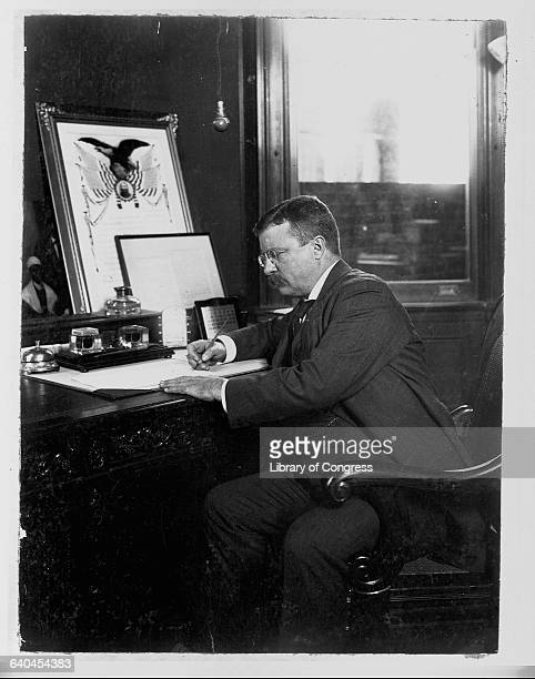 President Theodore Roosevelt signs a Thanksgiving proclamation in his office.