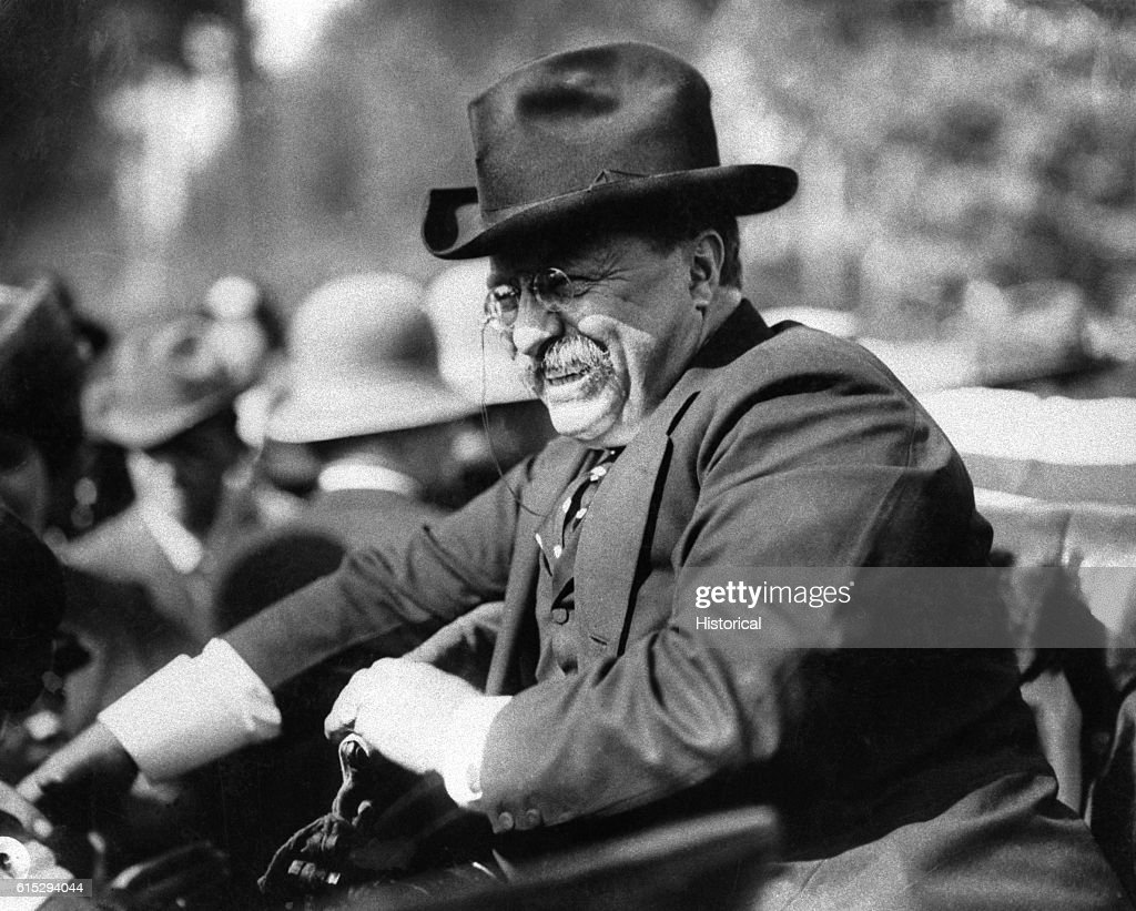 President Theodore Roosevelt (1858-1919), sitting in an automobile. Roosevelt succeeded as president after the death William McKinley and served for nine years, during which he began construction on the Panama Canal. He also brought about the Treaty of Portsmouth which ended to the Russo-Japanese War, for which he won a Nobel prize for peace.