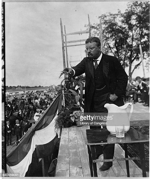 President Theodore Roosevelt speaks to a crowd from a stage.