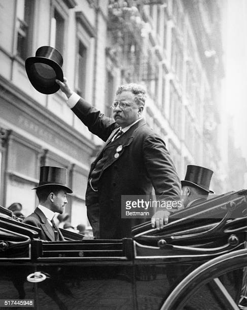 President Theodore Roosevelt waves his hat while standing in an automobile