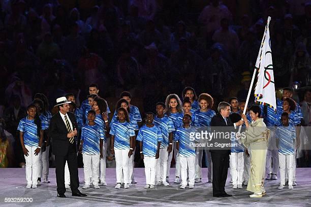 President Thomas Bach hands over the IOC flag to Governor of Tokyo Yuriko Koike while the Mayor of Rio de Janeiro Eduardo Paes watches on stage at...