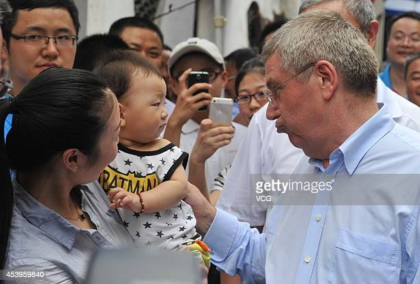 IOC President Thomas Bach interacts with a baby as he visits Gaochun Old Street during day six of the Nanjing 2014 Summer Youth Olympic Games on...
